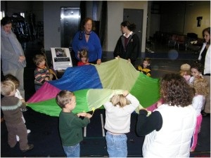 """""""All the fish are swimming in the water, bubble bubble bubble bubble SPLASH!"""" Here children take turns going under the parachute to act out their favorite undersea creatures: dolphins, sea turtles and sharks all make an appearance."""