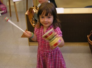 A four year old creates a percussive beat on an African hand drum.