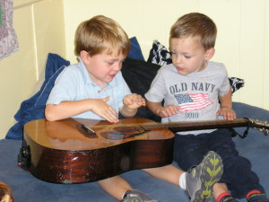 Gently and carefully, two four year olds explore the strings of an acoustic guitar.