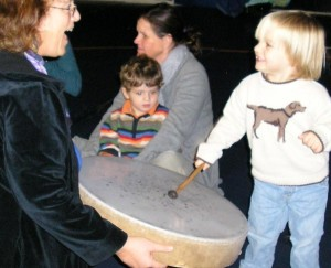 A two year old delights in creating a pattern on the frame drum.