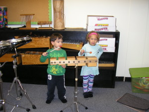 Two children create a simple accompaniment for Pop Goes the Weasel.